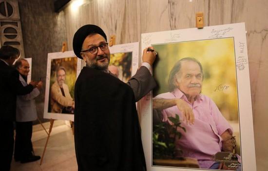 رییس دفتر در حال امضای یادگاری بر تصویری از سیروس ابراهیم زاده که نگاهی سراسر تأمل برانگیز دارد